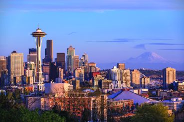 The City of Seattle's iconic skyline with Mount Rainier in the distance. The city is washed in the glow of a Pacific Northwest sunset.