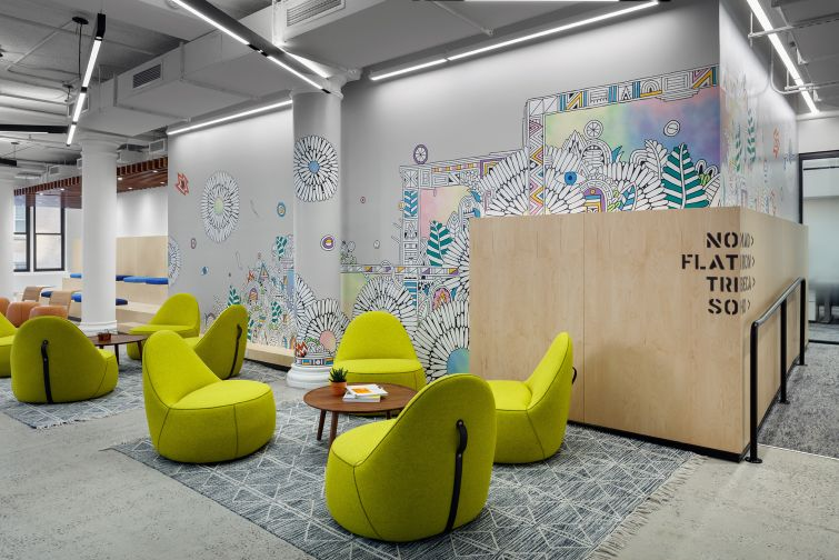 A colorful mural painted behind plywood is meant to be reminiscent of the city streets. Each part of the office is named after a city neighborhood, which is stenciled on walls or punched out of metal signs.