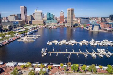 Aerial view of Baltimore's Inner Harbor area, with the Downtown skyline in the background.