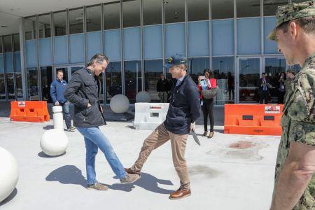 California Gov. Gavin Newsom, left, greets Los Angeles Mayor Gavin Newsom while practice social distancing.