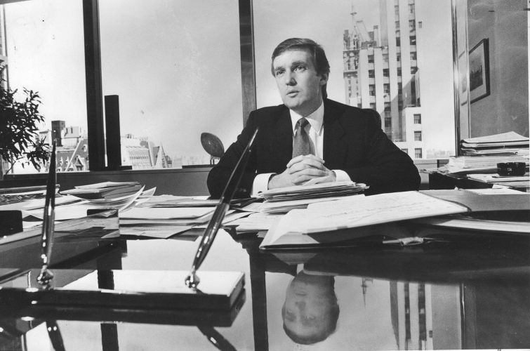 A man with his hands folded at the end of a long desk.