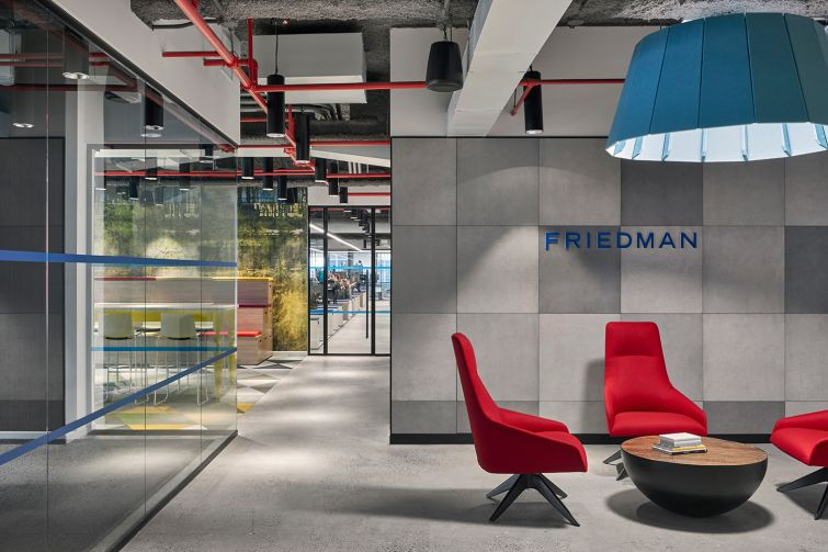 More primary colors in an open meeting space with red chairs and a blue light fixture.
