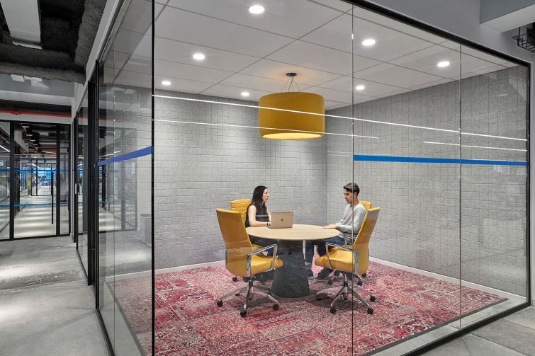 Yellow chairs and a light pendant help add interest to this conference room, which also has an overdyed rug.