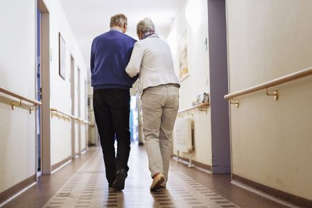 Senior Couple walking in a senior home.