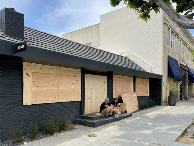 Buck Mason at 107 North Larchmont Boulevard has its windows and doors boarded up.