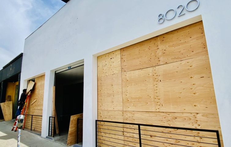 A vacant retail property is boarded up on Melrose Avenue in Los Angeles during the recent civil unrest.