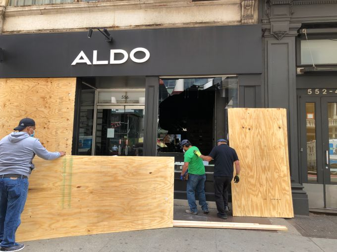 Workers board up a damaged Aldo store on Broadway in the wake of the May 31 George Floyd/Black Lives Matter protests.
