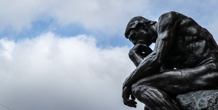 """The sculpture """"The Thinker"""" (""""Le Penseur"""") by the sculptor Auguste Rodin can be seen against a cloudy sky."""