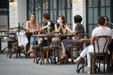 The federal unemployment rate has fallen as New York and other states reopen after coronavirus-induced business closures. Here, masked New Yorkers sit outside at The Smith on the Upper East Side.