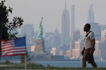 NEW YORK, NY - JULY 04: A citizen wearing a face mask walks by a beach on Independence Day on July 4, 2020 in New York City. Americans across the country celebrated Independence Day amid the spread of the coronavirus (COVID-19) pandemic. (Photo by Liao Pan/China News Service via Getty Images)