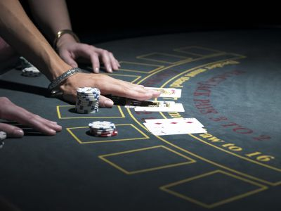 Two women playing Blackjack at gaming table, close-up
