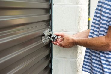 A customer unlocking a storage unit at a self-storage complex.