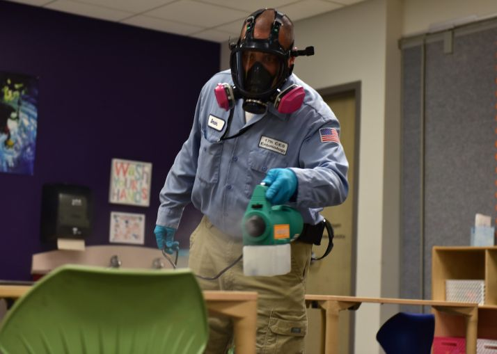 17th Civil Engineer Squadron pest controller Omar Martinez, walks around a classroom dispersing a disinfectant mist on all surfaces at Goodfellow Air Force Base, Texas, March 30. The chemical used is reportedly 99.99 percent effective at bonding to germs on the surface and killing them within the dwell time of 20 minutes. (U.S. Air Force photo by Senior Airman Seraiah Wolf)
