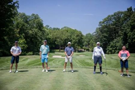 Five men on a golf course, spaced apart.