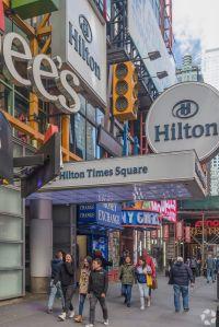 A colorful, busy hotel entrance on a sidewalk.