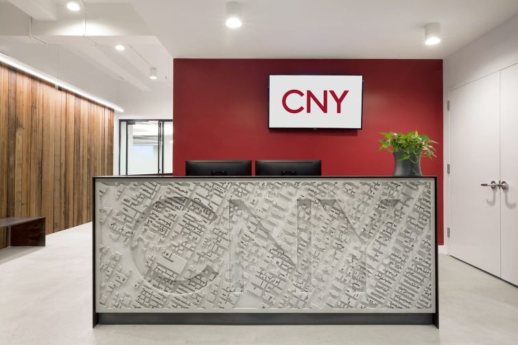CNY Group designed a concrete reception desk that's been stamped with an aerial map of Midtown Manhattan and the company's name.