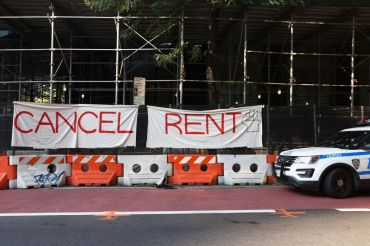 "A banner sign on scaffolding that says ""cancel rent."""