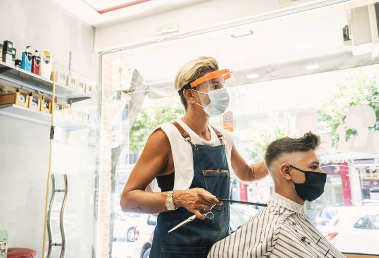 Barbershops and hair salons must practice physical distancing and use face coverings for both employees and customers.