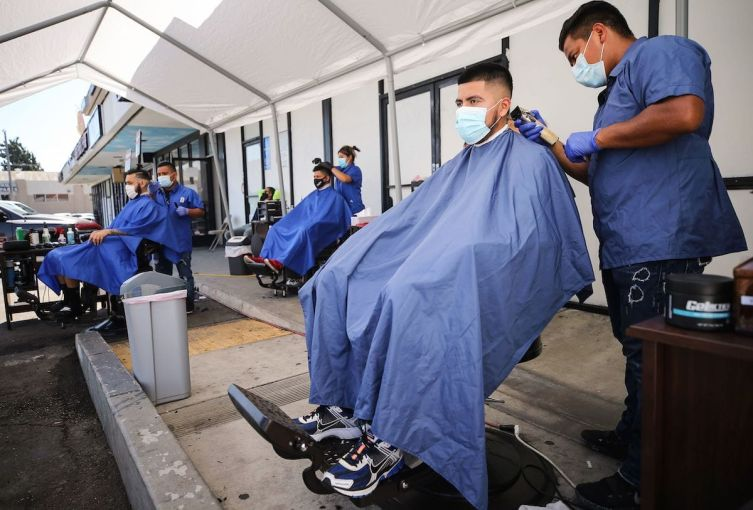 Barbers from King's Cutz in L.A. give haircuts beneath an awning outside. This week, barbershops and hair salons in L.A. can move operations indoors at 25-percent capacity, but they are encouraged to operate outdoors as much as possible to prevent the spread of coronavirus.