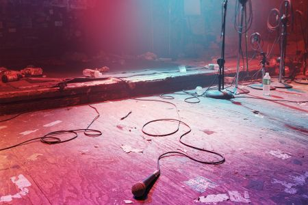 An empty, darkened stage with just a mic lying on top of it.