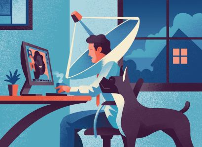 A man sitting at a desk with a dog next to him, and the man has a satellite dish around his head.