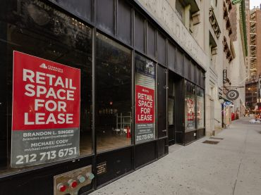 Empty storefronts with leasing signs on them along an empty sidewalk.