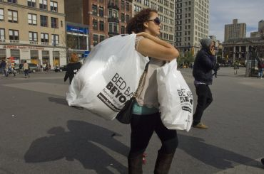 A woman carrying full plastic bags across a street.