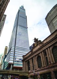 A glassy building viewed from far away on the street.