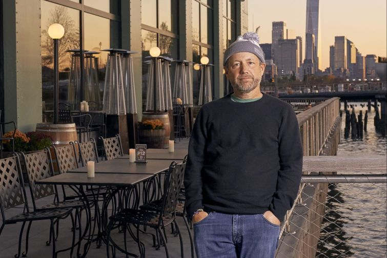 A man standing on a piece in front of some tables with tall buildings in the background.
