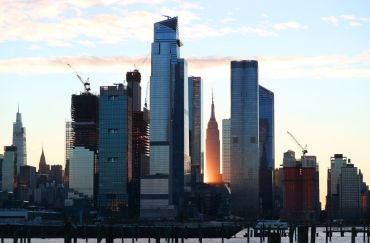 A photo of very tall buildings collected against a sunset.