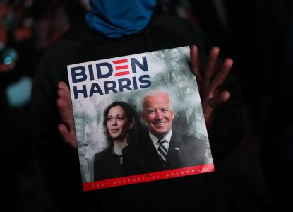 Two hands holding a sign that says Biden/Harris.