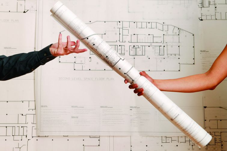 One arm handing off a rolled-up blueprint to another arm.