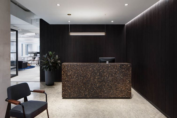 The reception area features blackened wood walls and a wood terrazzo desk.