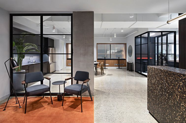 Swiss energy company Axpo Holding AG's new office incorporates midcentury modern furniture and a minimalist color scheme with pops of orange and blue.
