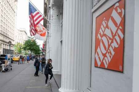 """The outside of a store on a busy city street, and the outside has a sign that says """"Home Depot."""""""