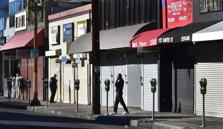 A man speaks on his cellphone in front of a row of shuttered small businesses in Los Angeles.