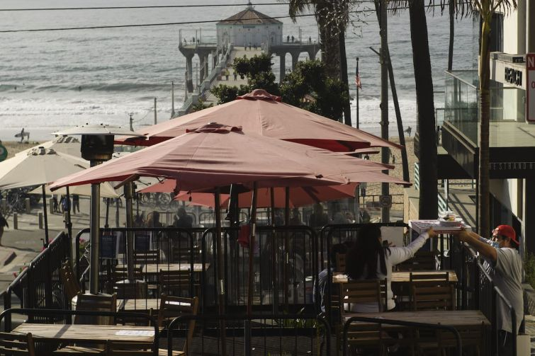 """People eat takeout food at a """"public parklet"""" due to COVID-19 restrictions on restaurant outdoor dining in Manhattan Beach, Calif."""
