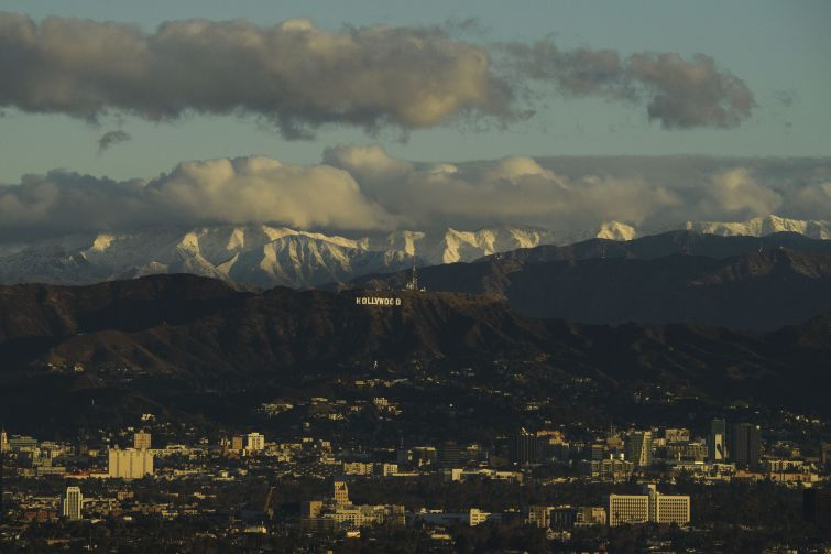 Snow-topped mountains stand behind the Hollywood Hills following heavy rains as seen from the Kenneth Hahn State Recreation Area on December 29.