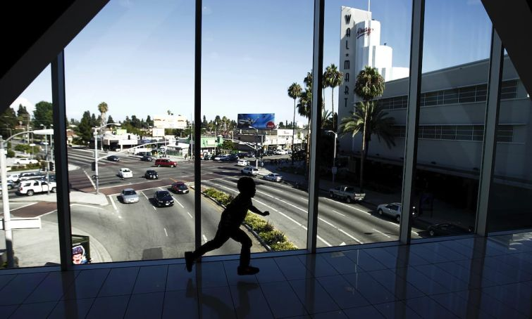 A child runs across a pedestrian bridge connecting separate parts of the Baldwin Hills Crenshaw Plaza shopping center in 2015. Another pending nine-figure deal for the landmark shopping mall has again been terminated this year due to community pressure.