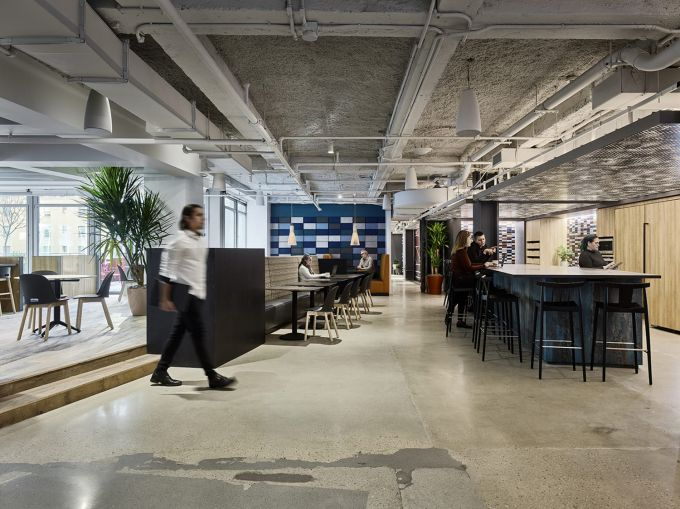 The main common spaces are somewhat industrial, with polished concrete floors and open ceilings painted gray.