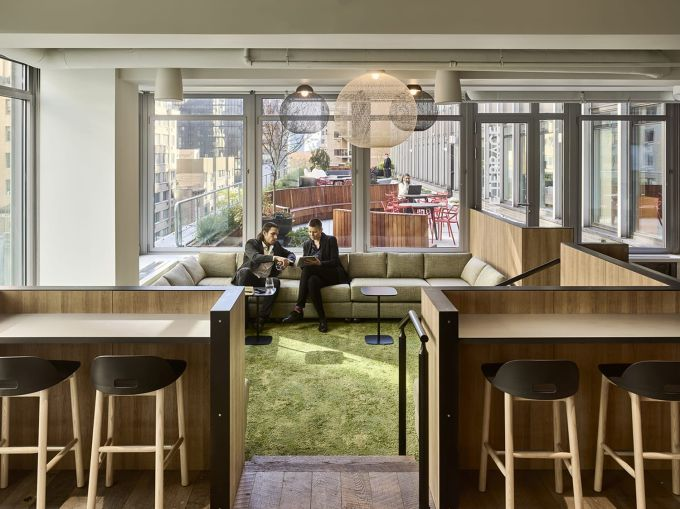 """Work spaces are organized into """"neighborhoods"""" themed around different colors, like green, blue and teal."""