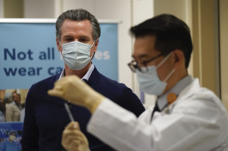 "Gov. Gavin Newsom watches as the Pfizer-BioNTech COVID-19 vaccine is prepared by Director of Inpatient Pharmacy David Cheng at Kaiser Permanente Los Angeles Medical Center. Newsom and legislative leaders said ""work is far from over"" for protecting renters in the state."