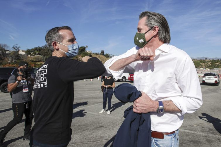 Los Angeles Mayor Eric Garcetti, left, greets California Governor Gavin Newsom at the launch of mass Covid-19 vaccination site at Dodger Stadium on January 15.
