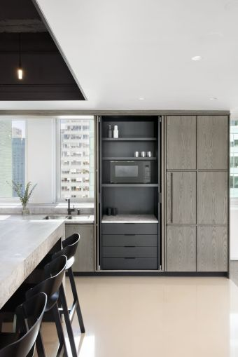 The space features a floor-to-ceiling wood cabinet that slides open to reveal an office pantry.