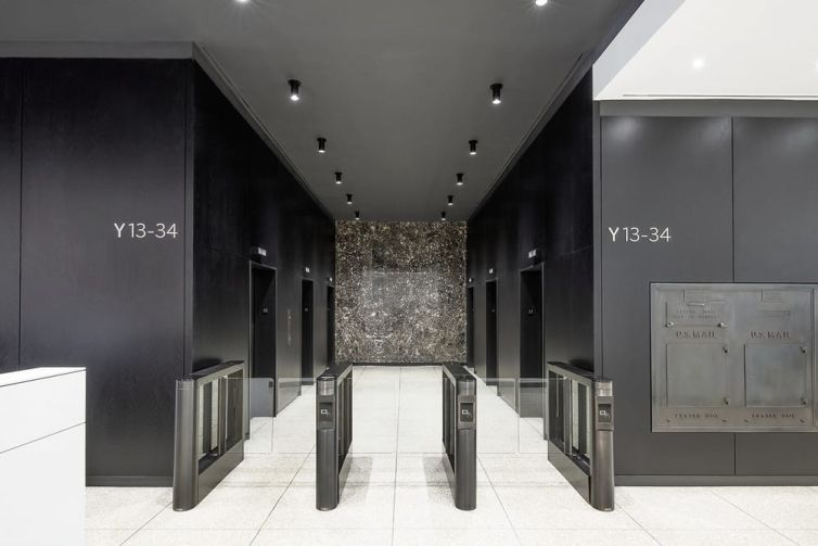 Black-stained wood panelling strikes a dramatic contrast for the ceiling and walls of the elevator banks.