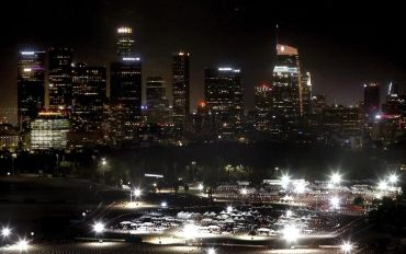 The Dodger Stadium testing and vaccination site overlooked by Los Angeles' skyline.