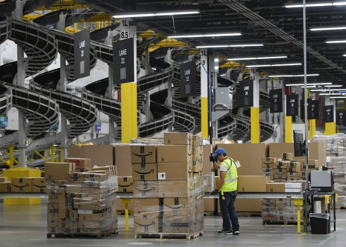 A warehouse associate wraps plastic around a pallet load of boxes at Amazon's fulfillment center. Demand has increased for industrial warehousing assets that support quicker supply chains, as well as supply chains that can move single items rather than large items or containers.