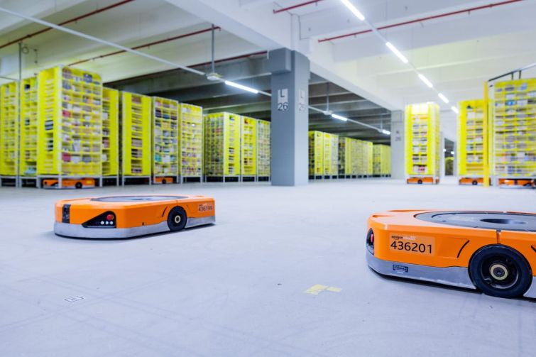 08 December 2020, North Rhine-Westphalia, Mönchengladbach: Robots transport goods to the employees in the warehouse of a logistics center of the mail order company Amazon.