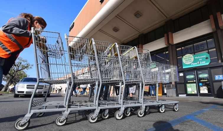 """A Food 4 Less employee pushes carts past supermarket workers gathered to protest in front of the supermarket in Long Beach after a decision by Kroger to close two supermarkets rather than pay workers an additional $4 in """"hazard pay."""""""