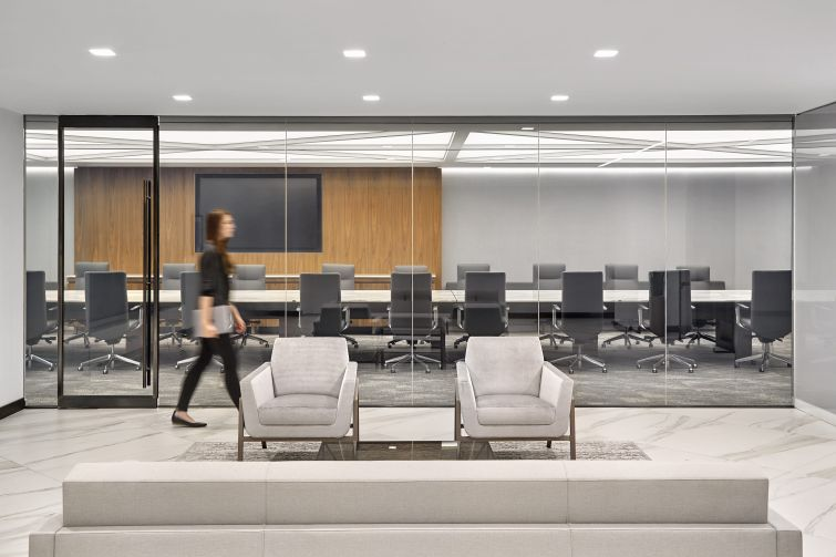 Conference and board rooms have wood panels on the walls, as well as unique furniture like this marble conference table that has an engraving that matches the pattern of the ceiling lights.